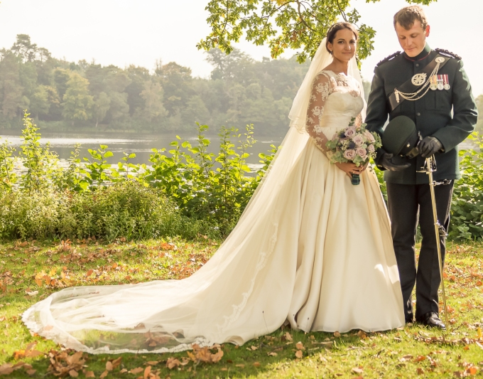 Wedding dress by Felicity Westmacott in ivory silk organza and corded lace, full skirt and lace bodice overlay with sash and long sleeves: long lace edged veil